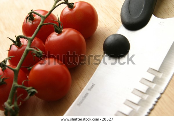 tomatoes and knife on wooden support