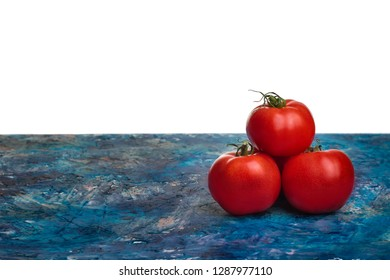 Tomatoes lying on the worktop and place for text. Three ripe vegetables. Pyramid from tomatoes.