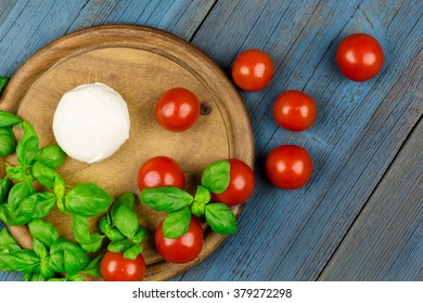 Tomatoes, mozzarella and basil on a cutting board on blue wood