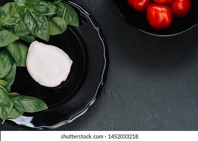 Tomatoes, mozzarella cheese and basil on dark stone background, top view, copyspace. Traditional Italian Caprese Salad, italian mediterranean food.