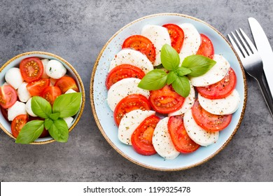 Tomatoes, mozzarella cheese, basil and spices on gray slate stone chalkboard. Italian traditional caprese salad ingredients. Mediterranean food.