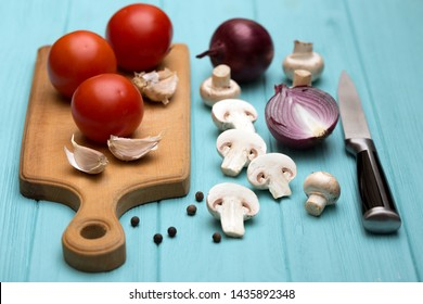 tomatoes, mushrooms, garlic on a cutting board on a blue background