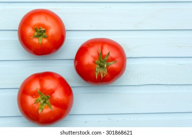 Tomatoes on blue wooden background