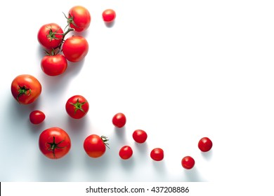 Tomatoes on a branch and cherry on a white background horizontal