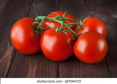Tomatoes on a branch. Tomatoes on the vine and on a brown wooden background. five tomatoes. Beautiful tomatoes with a beautiful green branch