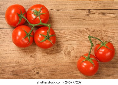 Tomatoes on Vine Isolated on a Wooden Background