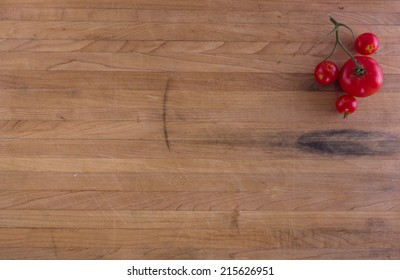 Tomatoes on a worn butcher block counter