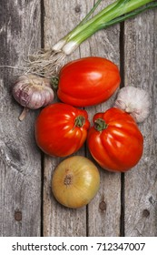 Tomatoes, onion and garlic on the vintage wooden table
