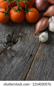 Tomatoes, onions and garlic on a rustic wood kitchen table. Vertical format with copy space.