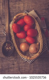 Tomatoes and onions on a old wooden background.