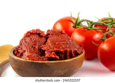 Tomatoes paste witTomatoes paste with ripe tomatoes isolated on white background. Tomatoes with a dish of tomato paste garnished. Fresh homemade tomato sauce.