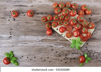 Tomatoes and pepper in groups with leaves of basil on the light wooden board and brown wooden table. As a frame.