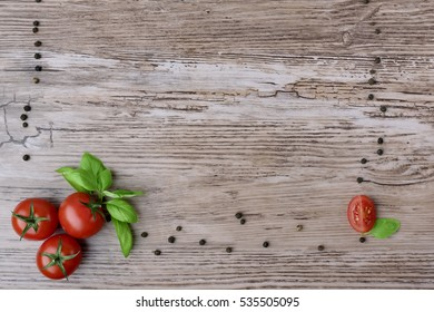 Tomatoes and pepper groups with leaves of basil on the brown wooden table. As a part of the frame.