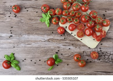 Tomatoes and pepper groups with leaves of basil on the light wooden board and brown wooden table. As a frame.