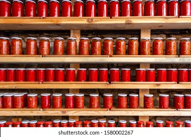 Tomatoes and pepper paste in jars. Tomato paste jars lined up on shelves. Tomato and pepper sauce
