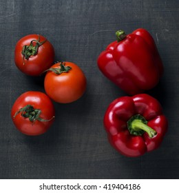 tomatoes and peppers over wooden background