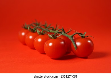 Tomatoes portrait concept with a grape of fresh cherry tomatoes close up view on red background.