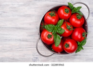 tomatoes in a pot on a white wooden table