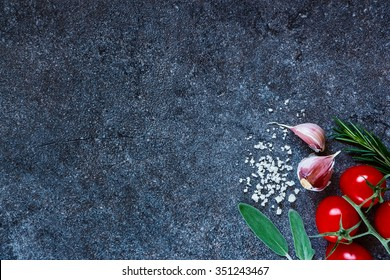 Tomatoes with sea salt, garlic cloves and fresh herbs on dark slate background. Organic vegetables. Cooking, Healthy Eating or Vegetarian concept. Top view.