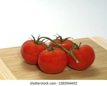 tomatoes, shrub tomatoes with stems, large, on a wooden board against a white background
