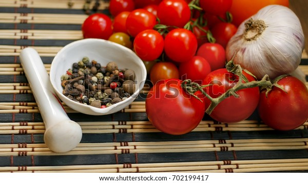 Tomatoes. Small cherry tomatoes and pepper. On the mat.
