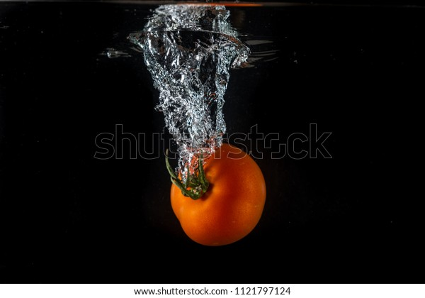 Tomatoes splashing in water on a black background