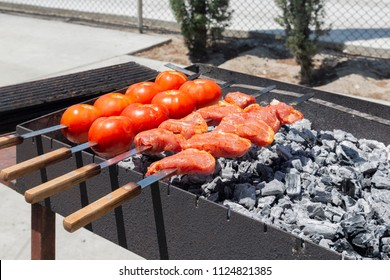 tomatoes and stakes on a barbeque grill in a back yard