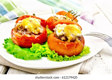 Tomatoes stuffed with meat and rice with cheese on lettuce in a plate, towel, fork on a wooden plank background