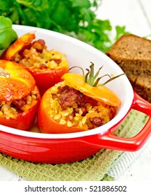 Tomatoes stuffed with meat and steamed wheat bulgur in a roasting pan on a napkin, bread and parsley on a wooden board background