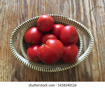 Tomatoes in a sweetgrass basket on a wooden table