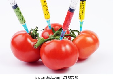 Tomatoes and syringes with different color liquids in them