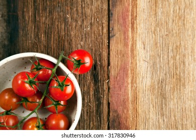 tomatoes in white bowl on old wood background