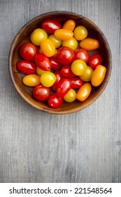 Tomatoes in a wooden bowl , little colorful red orange yellow tomatoes. on a wooden back ground.