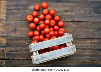 Tomatoes in a wooden box on a wooden table. Scattered tomatoes.