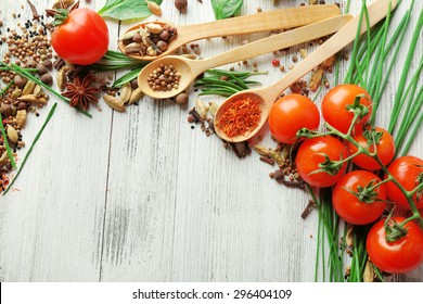 Tomatoes, wooden spoons with fresh herbs and spices on wooden background