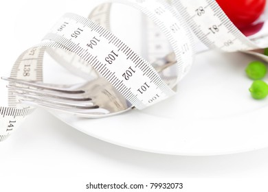 tomato,fork ,peas and measure tape on a plate isolated on white