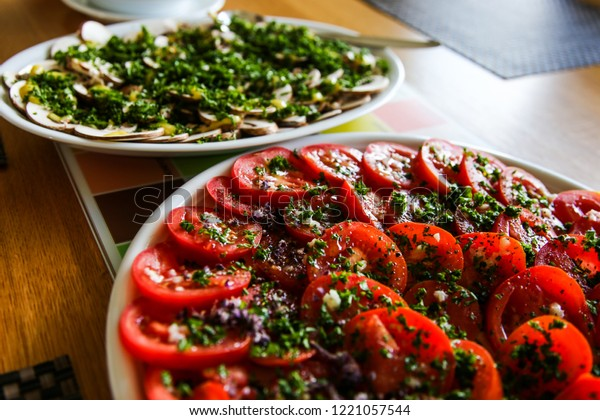 Tomatos and Mushrooms with a dressing and fresh herbs; snack for a BBQ; healthy and good food