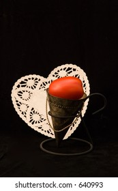 "Tomatos in a tin cone on an iron stand, on black background, with white doily (connotes the tomato's other name of ""love apple"").  Depth of Focus is somewhat shallow, and is on the tin cone/tomato."