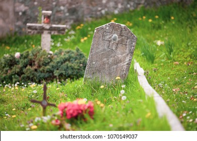 Tomb with stone cross and burial in a green meadow. Italian cemetery of Christian religion. Small empty oval frame.