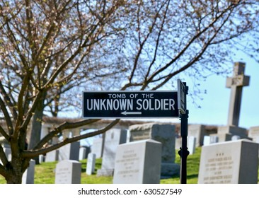 Tomb of the unknown soldier sign at Arlington National Cemetery in Washington D.C. with gravestones and headstones and bare tree branches in the background.