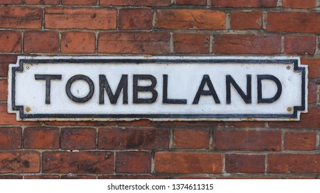 Tombland Street Name Sign on Brick Wall, Shallow Depth of Field horizontal photography