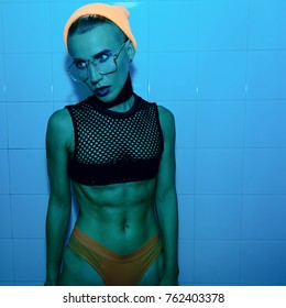 Tomboy Girl in fashion look. Fashion accessory glasses, beanie and choker. Top mesh. Stylish neon light