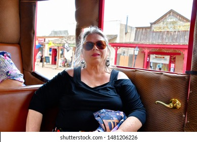 Tombstone, Arizona / USA - 11 August 2019 Mature woman sitting inside a stagecoach taking a tour of Tombstone Arizona