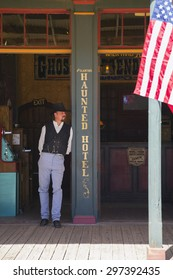 Tombstone, Arizona, USA, April 6, 2015, cowboy and flag in old western town home of Doc Holliday and Wyatt Earp and Gunfight at the O.K. Corral