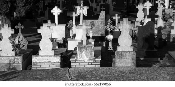 Tombstone with candles and aged stone cross, cemetery