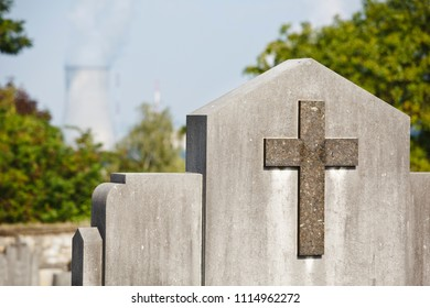 A tombstone with a cross on a cemetery, a nuclear power station in the background. Taken in Huy, Tihange, Belgium.