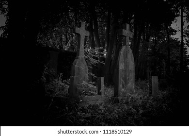 Tombstone and graves in an ancient church graveyard in the darkness