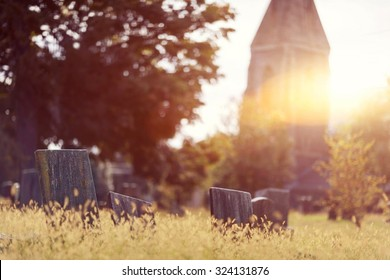 Tombstone and graves in a church graveyard in the fall