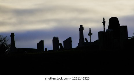 Tombstones in a village graveyard silhouetted against the evening sky