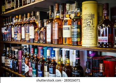 TOMINTOUL, UK - MAY 16: Various bottles of Scotch whisky on the shelf on May 16, 2015 in Tomintoul, UK. Scotch whisky must be made in a manner specified by law.